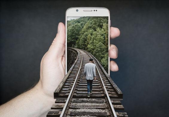 Mobil Phone in der linken Hand, Mann geht auf Bahngleis