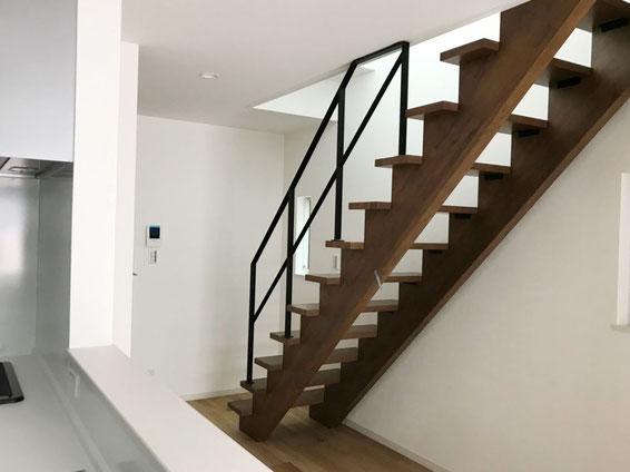 木製のストリップ階段と真っ白なクロスと黒いスチール手すり