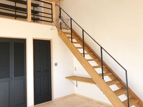 木製のストリップ階段に星型のペンダント照明、黒のアイアン手すりをささらに取付
