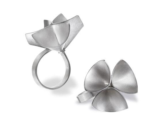 Der wunderbar außergewöhnliche Ring TALLA ist aus feinstem, weißlich schimmerndem Silber gearbeitet. Die apart dreidimensional ausgearbeitete Form erinnert an eine Blüte oder ein Kleeblatt.