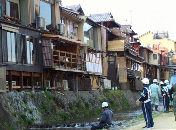 Ouvriers en train de désherber et nettoyer le canal sous les terrasses des cafés de Ponto-chō