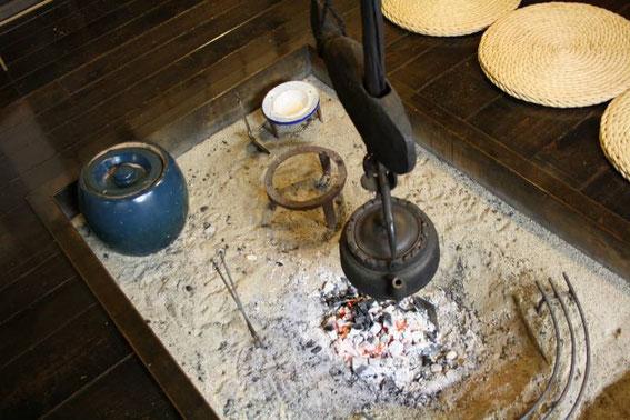 L'eau du thé chauffe doucement sous son poisson-crémaillère
