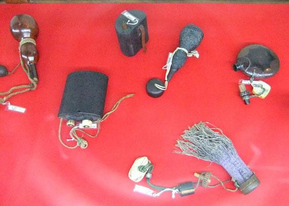 """En haut, cinq modèles de """"poires"""" à poudre. A droite en bas, des mèches et le """"briquet"""" d'allumage"""