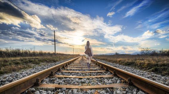 ギターを持って線路を歩く女性