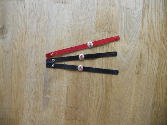 Bracelets en cuir, fermoir réglable, croix argentée et rouge, 16 euros.