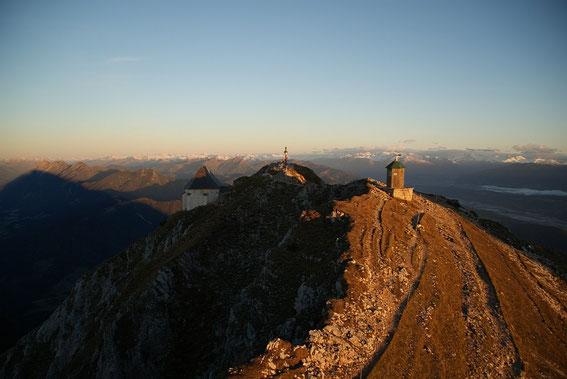 Die ersten Sonnenstrahlen am Gipfel, im Hintergrund wieder die Hohen Tauern