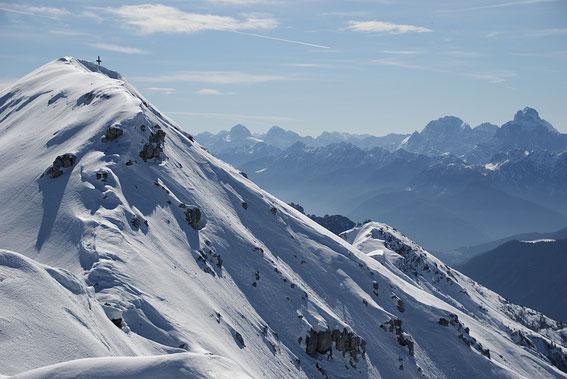 Der Blick vorbei am Gipfelkreuz in die Julischen Alpen; ganz rechts Montasch und Wischberg, links Mangart und Jalovec