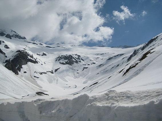 Der Blick vom Parkplatz hinauf zum angestrebten Ziel (Bildmitte), der Aufstieg erfolgt durch das Tal, dann die weite Mulde im rechten Bildteil und zuletzt über die weiten freien Hänge