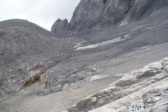 Blick über den Ansatz der Gletscherzunge zum Eisscheitel. Der graue Firn unterscheidet sich in der Farbe kaum von der Schuttbedeckung.