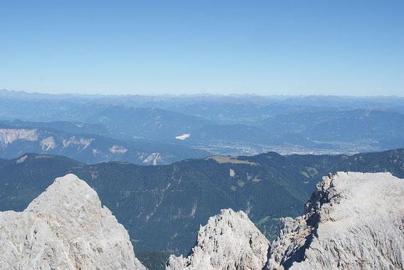 Im Norden zeigt sich im Tal Villach und am Horizont erhebt sich hinter den Nockbergen der Dachstein