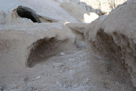 Der untere Teil des Gletschers ist mit Sand und Schutt bedeckt, das Gletschertor mündet in einen Eiskanal