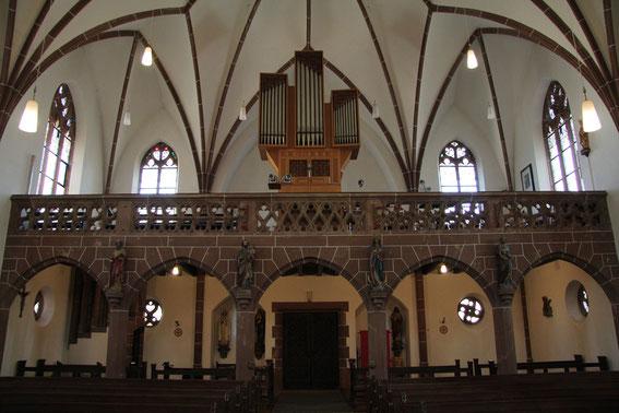 Pfarrkirche - Empore mit Orgel. Der Chor singt auf einer Tribüne, die sich zwischen der Orgel und der an der Wand befestigten Statue der Heiligen Cäcilia befindet. (Foto: Richard Seer, Wiltingen)
