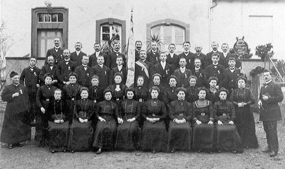 Der Kirchenchor im Jahre 1911 mit der Vereinsfahne. Links: Pfarrer Joseph Dehen (Dienstzeit: 1902-1924, Erbauer der Pfarrkirche). Rechts: Chorleiter Herr Stoll.