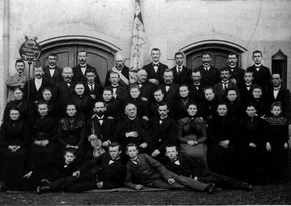 Der Kirchenchor im Jahre 1904 mit der Vereinsfahne. Herr Caspar mit Violine, rechts daneben Pfarrer Joseph Dehen (Dienstzeit: 1902-1924, Erbauer der Pfarrkirche), Chorleiter Herr Göbel (oben links).