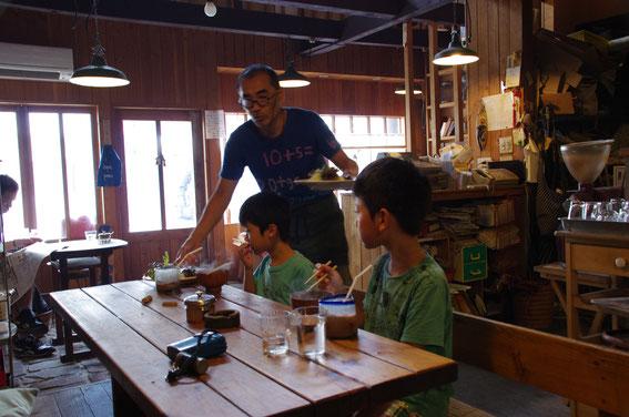 京都の喫茶店「西陣ほんやら洞」の「ゴーダさん」がランチのハンバーグを出しているところ。ゴーダさんは、今出川の「ほんやら洞」の中興の祖で、先代から引き継いだお店を長らく存続させた立役者。現在は西陣でお店を経営中(レジの脇に小誌あり)。最近はプールに行くのが忙しく、午後3時前にお店が閉まっちゃうので要注意。水曜がお休みです