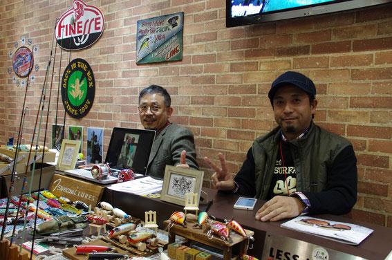 """今年のフィッシングショー大阪にて。小誌創刊号ベイトリール特集に御寄稿いただいた「Tunami Lures」の元木さん(左。右はLess is Moreの高橋さん)。独特の、メキシコチックでポップなカラーのプラグやロックでギターなデザインのベイトリールが展示されていた。""""Love Fishing, Music & Peace ! """""""