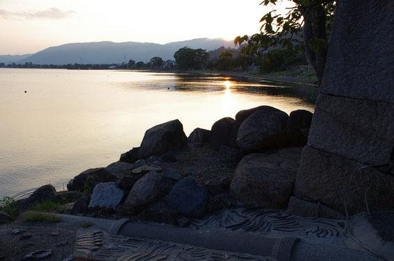 海津の向こうに沈む夕陽。右端のシルエットになっている石積みは「古道具&カフェ海津」のもの。国の「重要文化的景観」に指定されている、由緒ある石積みです