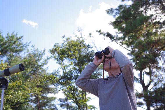 雲の合間をタカが滑空していく姿を観察中のサム山岡さん。愛用の双眼鏡は100年以上前に製造されたドイツ製。詳しくは小誌06号を、ぜひ御覧ください