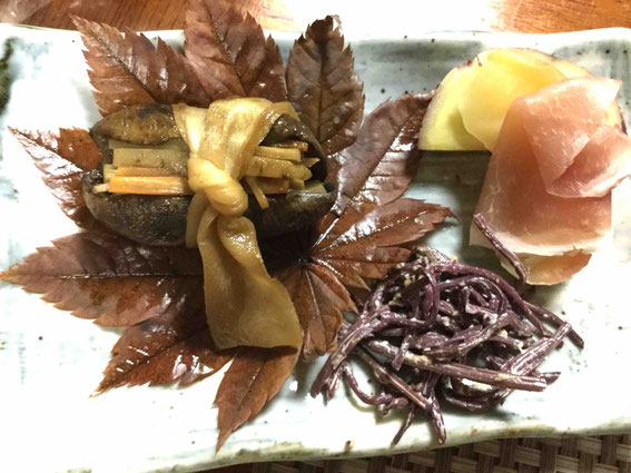 アケビの皮を干しておき、中に根菜類や一粒ずつ自分で潰した打ち豆を入れてかんぴょうで結び、煮る。さつまいもも自家製。右下は赤こごみ