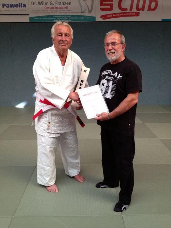 JC 66 Präsident Roland Assmann überreicht den rot-weißen Gürtel als Geschenk an           den neuen Träger des 6. Dan