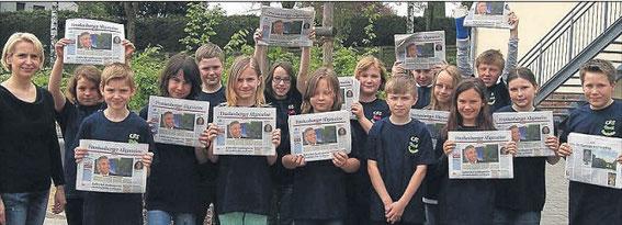 Sie halten die Zeitung hoch - Auch die Kinder der Klasse 4b der Cornelia-Funke-Schule Gemünden beschäftigen sich nun zusammen mit Klassenlehrerin Bianca Schneider (links) ausführlich mit der HNA.