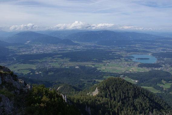 Der Blick hinunter zum Faaker See sowie auf die Stadt Villach, im Hintergrund die Nockberge