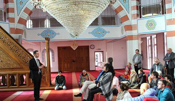 """Halil Sahin (links), Generalsekretär der Fatih Moschee in Pforzheim, erklärt den Besuchern bei der Führung durch das islamische Gotteshaus am bundesweiten """"Tag der offenen Moschee"""" den Gebetsraum."""