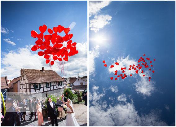 Hochzeitspaar lassen Luftballons steigen an der Dorfkirche in Neuberg fotografiert vom Hochzeitsfotograf Hanau und Gelnhausen.