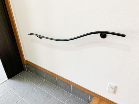 玄関に空間を引き締める、曲線がステキな壁付けアイアン手すり