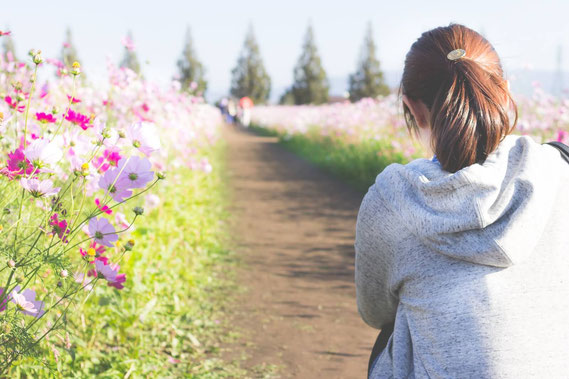 花に囲まれた道を歩く女性