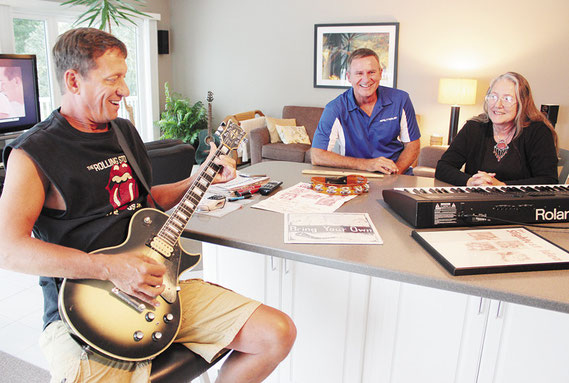 Jeff Theisen, Dave Valant and Jill Naegle, three of the original members of Slightest Idea, go over their songlist at the Theisen home south of town. The band will perform a set or two during Bellevue's Reunion on the River Saturday at Cole Park.