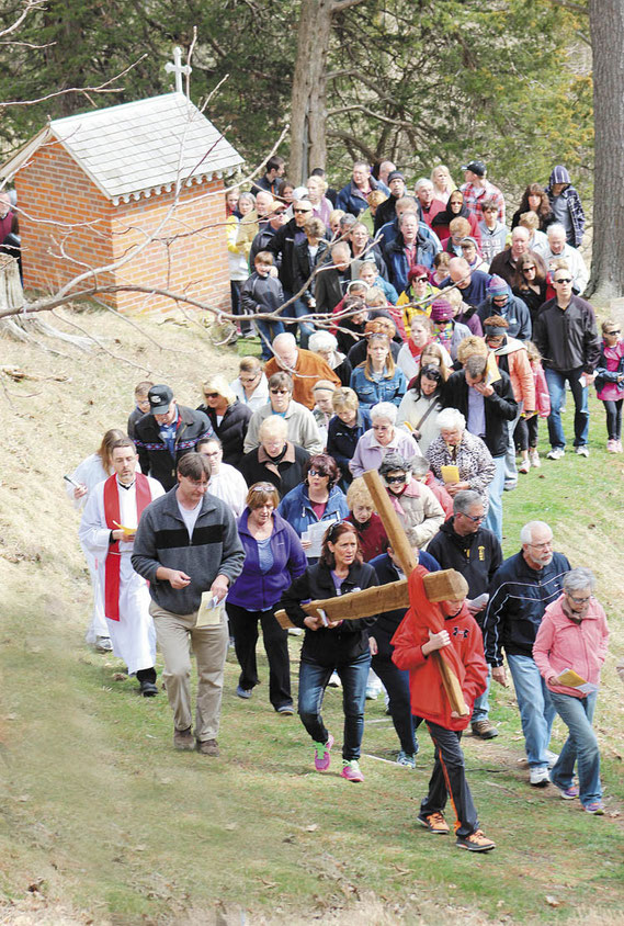 Hundreds attended the Outdoor Way of the Cross service in St. Donatus on Good Friday. Above, the cross is carried past the stations to the old Chapel on the bluff overlooking the church and the community.