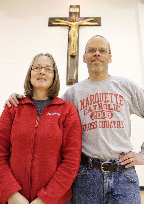 Chris and Kathie Lampe pose for a photo with the recently blessed, handcrafted crucifix now located in the gymnasium of the Marquette Education Center.