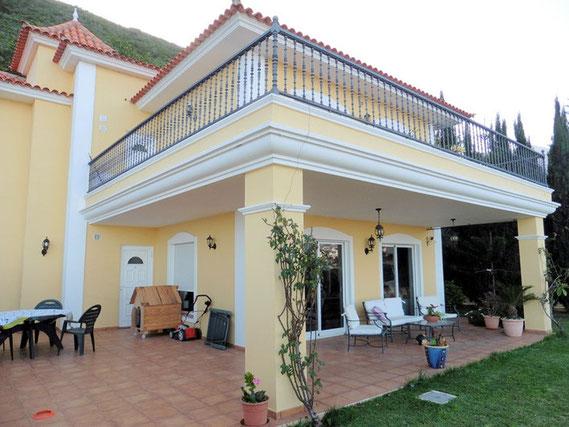 Blick vom Garten auf das 2 Stöckige Haus mit Terrasse und darüber einem Balkon. Die Immobilie ist im gelben Farbton gestrichen und die Fenster sind weiß eingefasst.