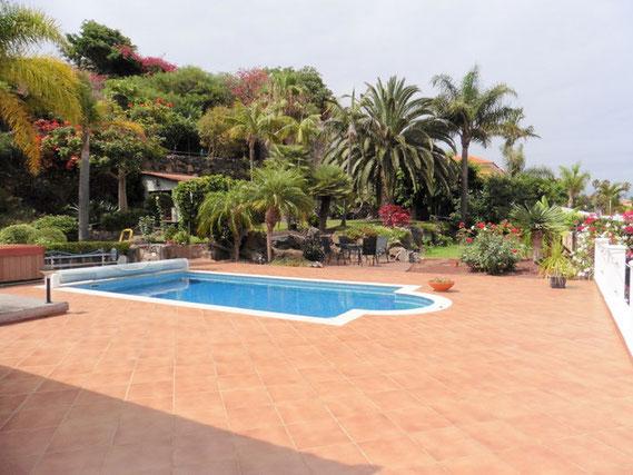 Pool mit Meerblick und tropischen Garten im Hintergrund.