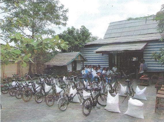 La distribution des vélos et des sacs de riz devant le Centre