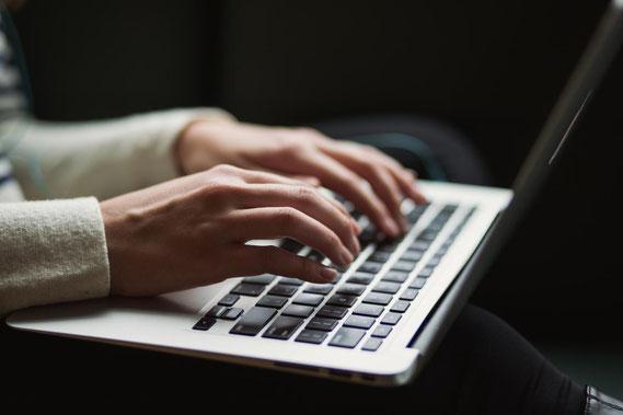 Frau schreibt auf Laptop: Werbung für den 2. Münsteraner Schreibmarathon im Schreibraum Münster.