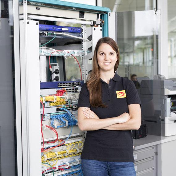 IT-Netzwerk: Elektrikerin steht vor einem EDV-Verteiler