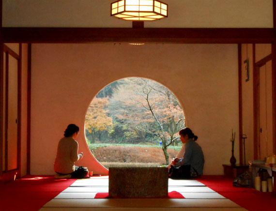 本堂方丈の丸窓から後庭園を見る女性二人
