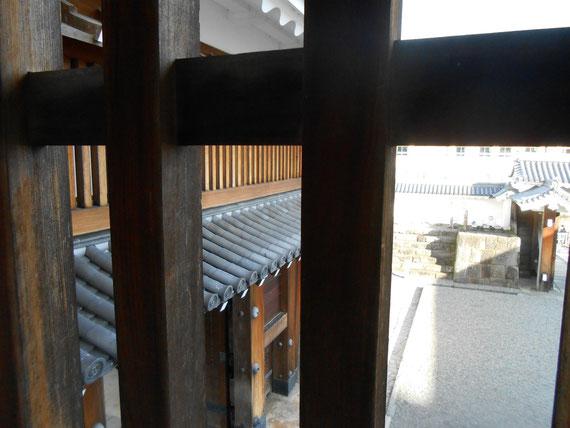 鉄砲狭間の格子から櫓門をみる