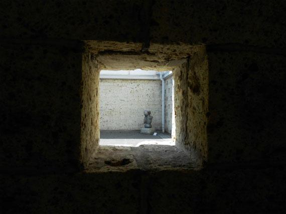 展示棟内部ホールから、大谷石の開口部から外部展示の彫刻を覗く