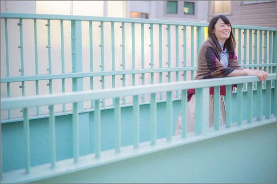歩道橋の上で笑う女性