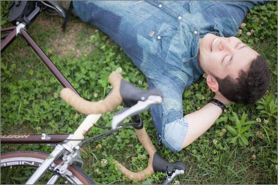 自転車を停めて横になる男性