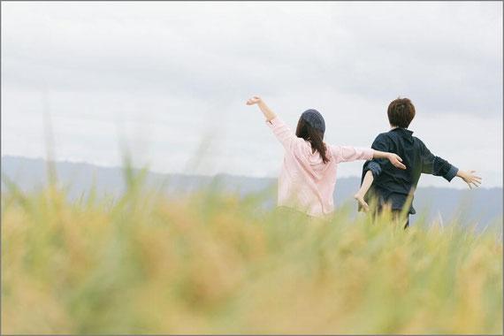 草原で手を広げるカップル