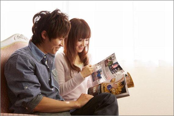 仲良く雑誌を見るカップル