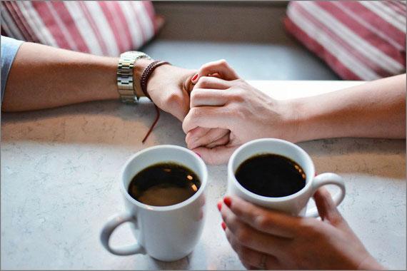 手をつなぐ男女とコーヒーカップ