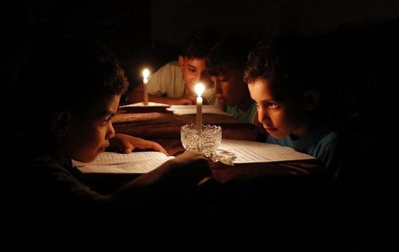Des enfants palestiniens lisent à la lumière des bougies en raison des pénuries d'électricité à Gaza, le 13 juin (AFP)