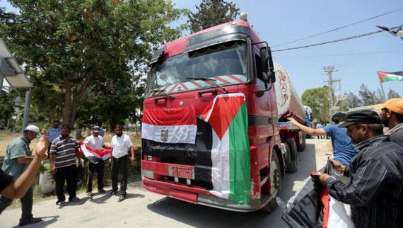 Des Palestiniens accueillent les camions-citernes avec des drapeaux égyptien et palestinien à Rafah, le poste-frontière entre l'Egypte et la bande de Gaza, le 21 juin 2017.