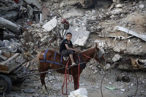 Un garçon palestinien monte un cheval devant les décombres des bâtiments qui ont été détruits pendant la guerre qui a duré 50 jours entre Israël et les combattants du Hamas pendant l'été 2014 (AFP)