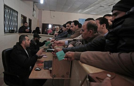 Des Palestiniens attendent des permis de voyage pour traverser la frontière de Rafah après son ouverture par les autorités égyptiennes pour les cas humanitaires en décembre 2016 (AFP)